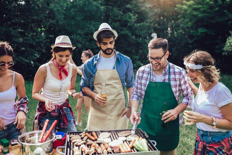 Des amis qui s'amusent à griller de la viande en profitant du barbecue photographie stock libre de droits