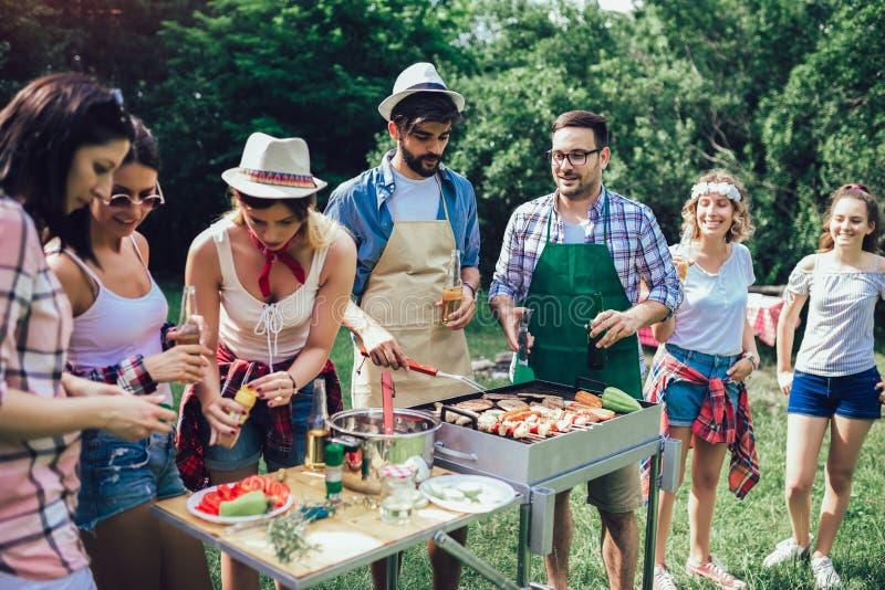 Des amis qui s'amusent à griller de la viande en profitant du barbecue image libre de droits