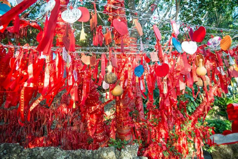 Des arbres grands est complètement décorés des rubans rouges beaucoup de rubans rouges attachés aux arbres l'asie photographie stock libre de droits