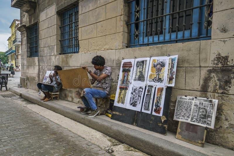 Des artistes de rue peignent des souvenirs dans la rue de La Havane à Cuba image libre de droits