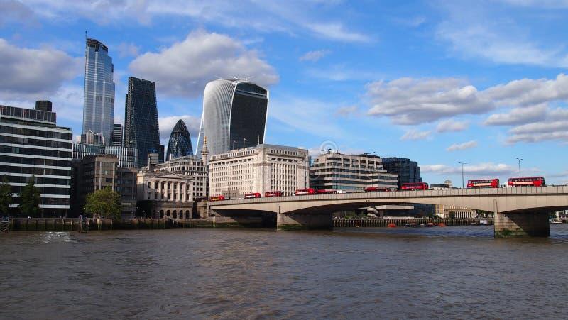 Des autobus à deux étages rouges traversant la Tamise au-dessus du pont de Londres, avec en arrière-plan les gratte-ciel de Fen photo stock