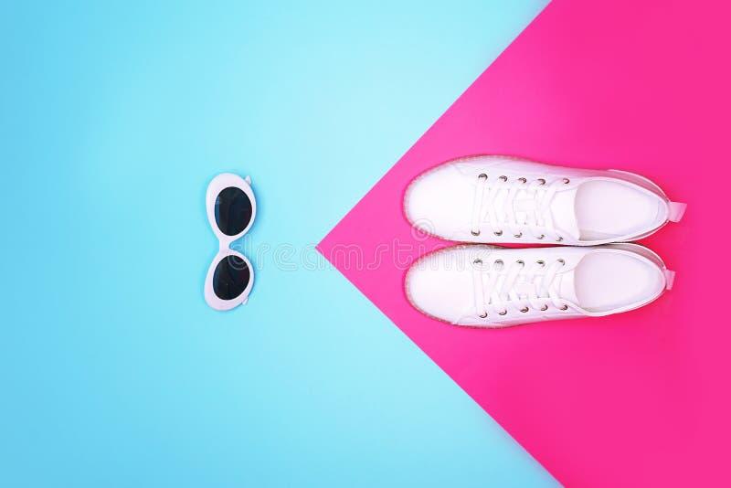 Des baskets blanches et des lunettes de soleil blanches sont posées sur un arrière-plan rose bleu couleur néon clair image libre de droits