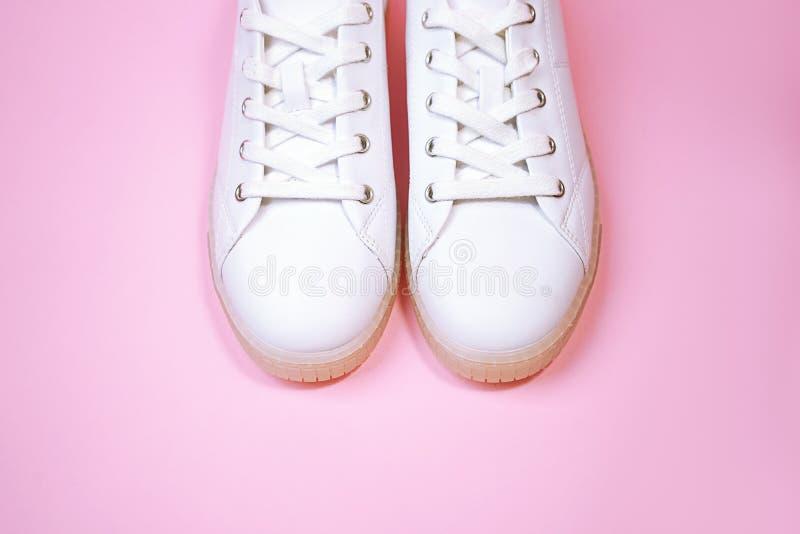 Des baskets blanches sont posées sur un fond rose pastel image libre de droits