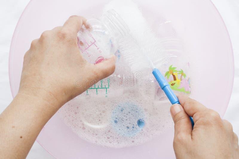 Des biberons il était clair qu'un désinfectant dans la solution de nettoyage de l'eau avec la brosse de bouteille photo libre de droits