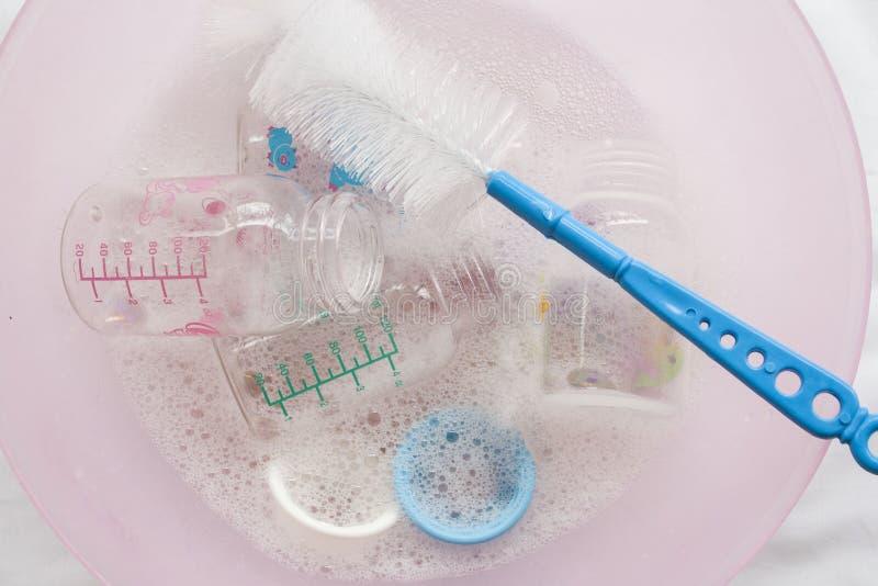 Des biberons il était clair qu'un désinfectant dans la solution de nettoyage de l'eau avec la brosse de bouteille photos libres de droits