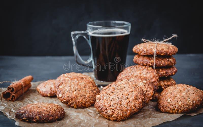 Des biscuits d'avoine sains faits maison avec de la cannelle et de la tasse de café en verre sur un parchemin brun Concept d'alim image libre de droits