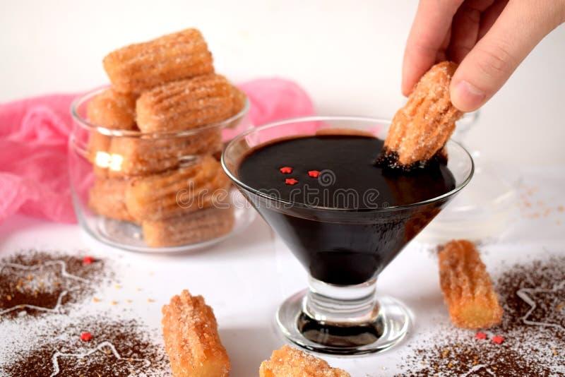 Des biscuits espagnols Churros sont plongés dans la crème au chocolat images libres de droits