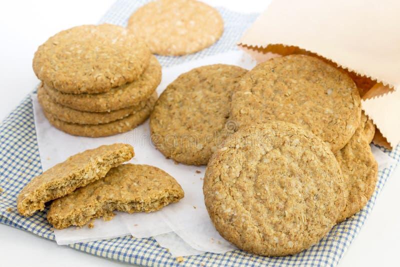 Des biscuits sablés faits maison faits de farine d'avoine sont empilés sur le tissu et dans le sac de papier sur le fond blanc de image libre de droits