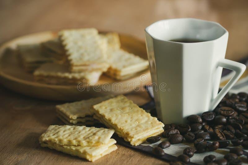 Des biscuits sont placés sur les plats et la tasse de café en bois avec les grains de café rôtis photo libre de droits