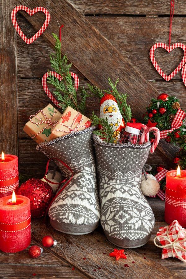 Des bottes avec des petits cadeaux et des bonbons photos stock