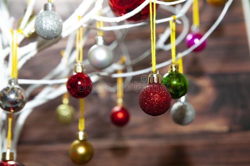 Des boules colorées ornements de noël accrochées à l'arbre de noël sur une planche en bois images stock