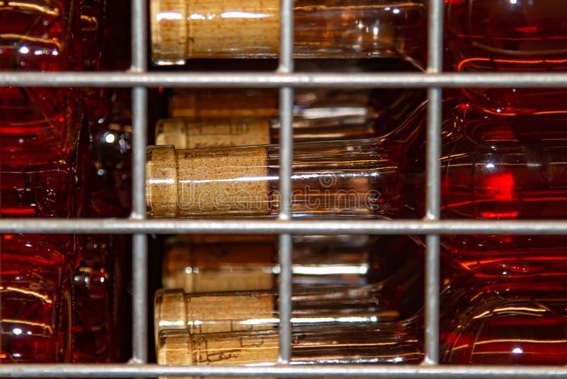 Des bouteilles avec du vin sont stockées dans une boîte squelettique photographie stock