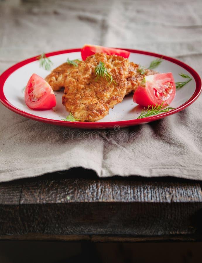 Des côtelettes de viande et de poulet juteuses et des tomates sur une assiette blanche sur un simple fond de lin clair, accompagn photographie stock libre de droits