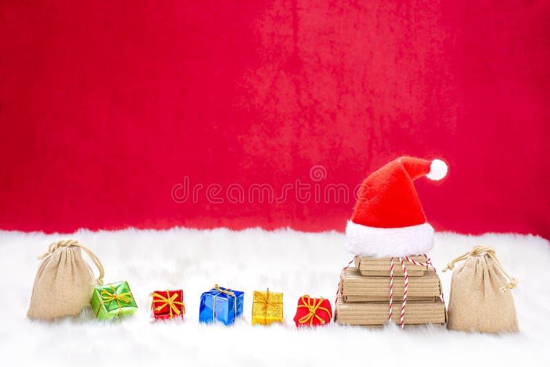 Des cadeaux de Noël colorés avec un chapeau de santa dans la neige photographie stock libre de droits