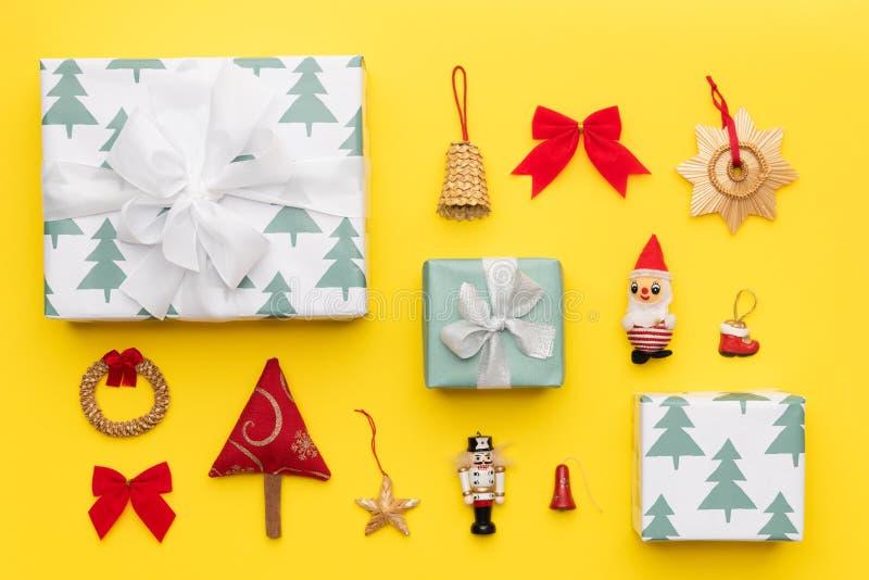 Des cadeaux de Noël enveloppés et de nombreux ornements rétro de noël isolés sur fond jaune vif Composition de Noël image libre de droits
