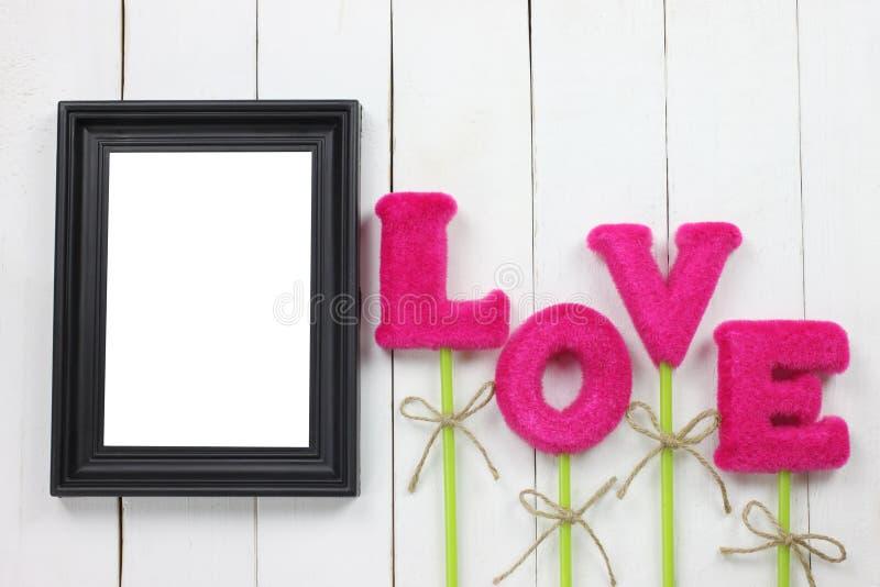 Des cadres de tableau et les lettres rouges de l'amour sont placés photo stock