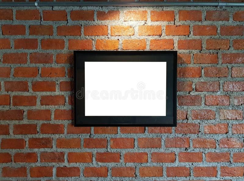 Des cadres de tableau noirs vides sont montés sur les murs de briques rouges avec c photographie stock libre de droits