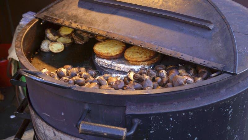 Des châtaignes rôties sont faites cuire dans un baril de fer images stock