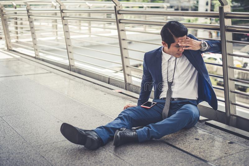 Des chômeurs d'homme d'affaires de la société s'asseyant sur la rue et sa tête étreinte par main, il est se sentir de soumis à un photos libres de droits