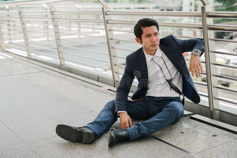 Des chômeurs d'homme d'affaires de la société s'asseyant sur la rue, il est des honoraires photographie stock libre de droits