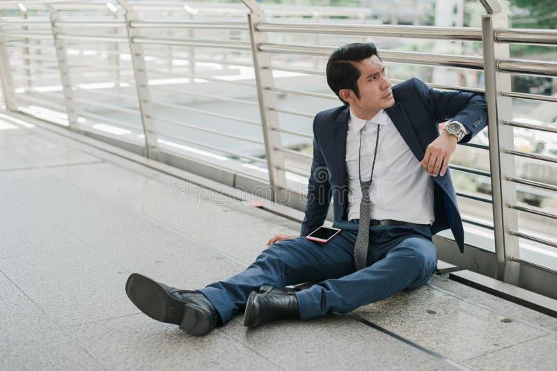Des ch?meurs d'homme d'affaires de la soci?t? s'asseyant sur la rue, il est se sentir de soumis ? une contrainte et la tristesse, images libres de droits