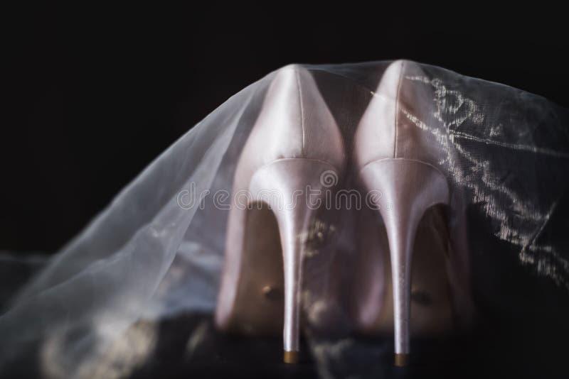 Des chaussures nuptiales beiges sont voilées image libre de droits