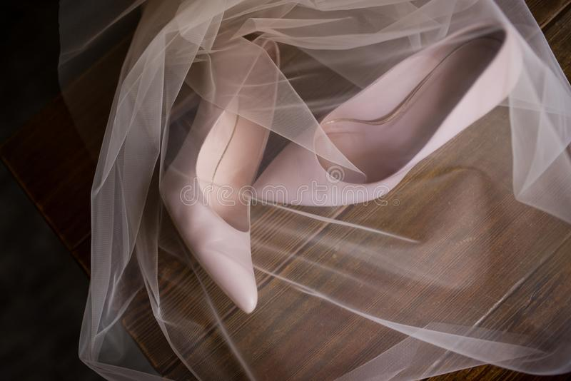 Des chaussures nuptiales beiges sont voilées mariage photos libres de droits