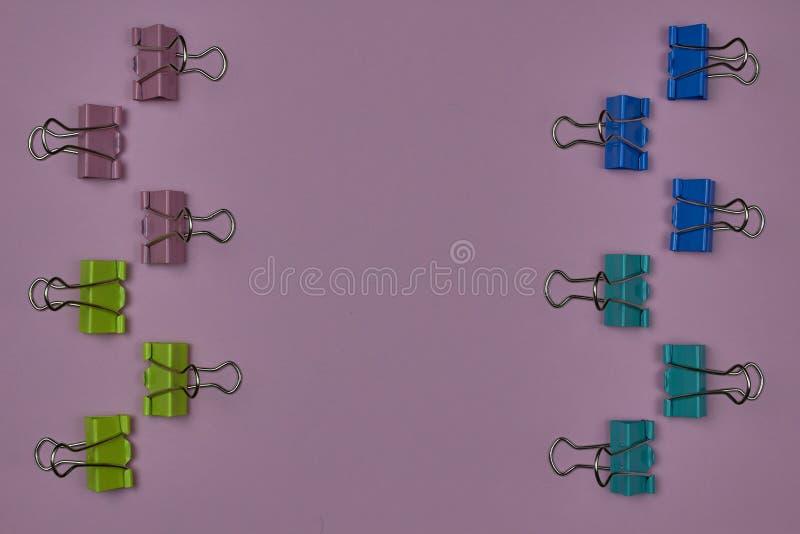 Des clips de papier rose, jaune, bleu et vert sur un fond rose avec espace de copie pour le texte photos stock