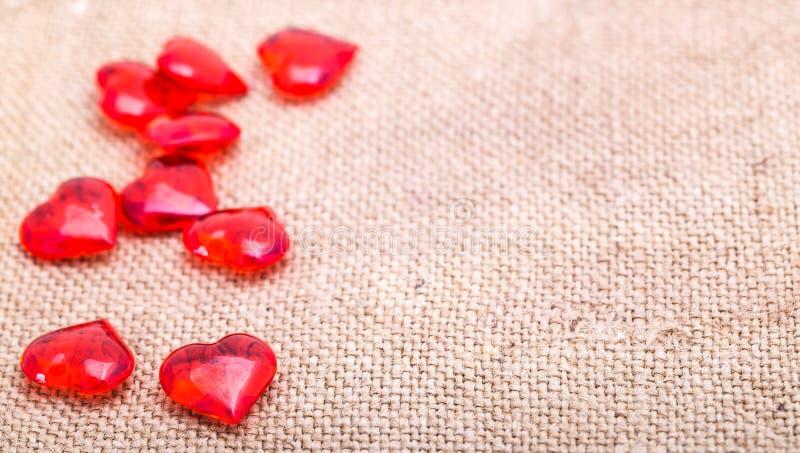 Des coeurs en verre rouges sont dispersés sur une serviette de renvoyer images stock