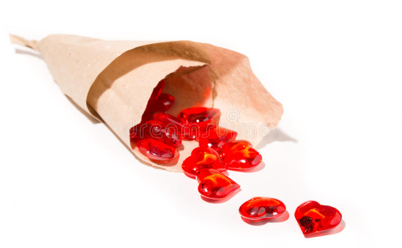Des coeurs en verre rouges sont versés d'un colis de papier images libres de droits