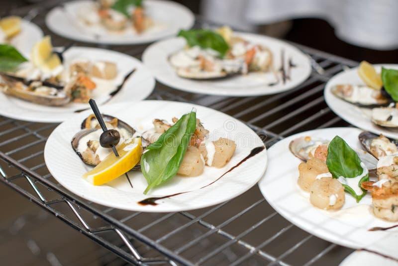 Des coquilles Saint-Jacques, une assiette de restaurant blanc aménagée de façon créative images stock