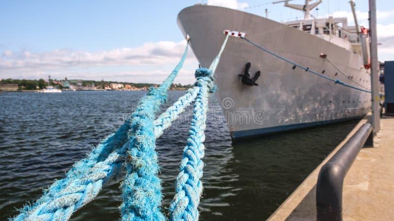 Des cordes d'amarrage sur une jetée avec le grand bateau, concept de voyage de vacances images libres de droits