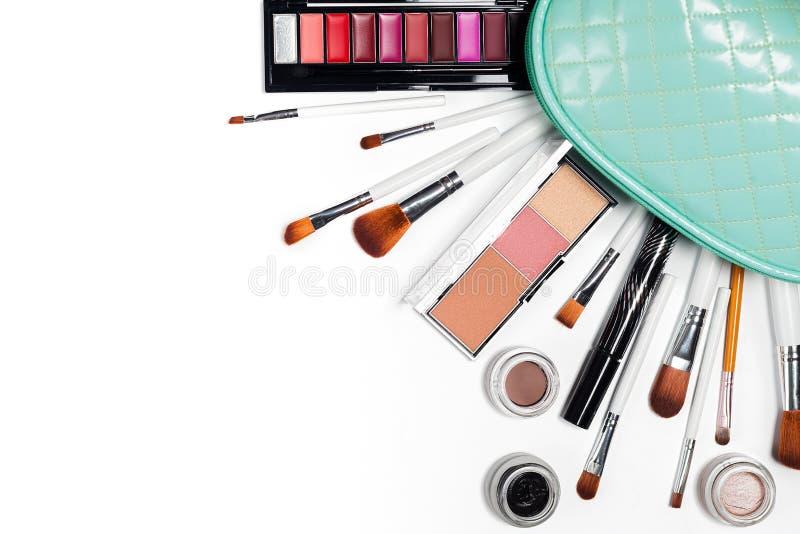 Des cosmétiques est versés d'un sac cosmétique, sacs à main sur un blanc image stock