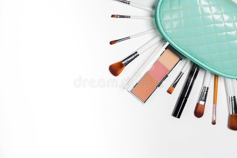 Des cosmétiques est versés d'un sac cosmétique, sacs à main sur un blanc photos stock