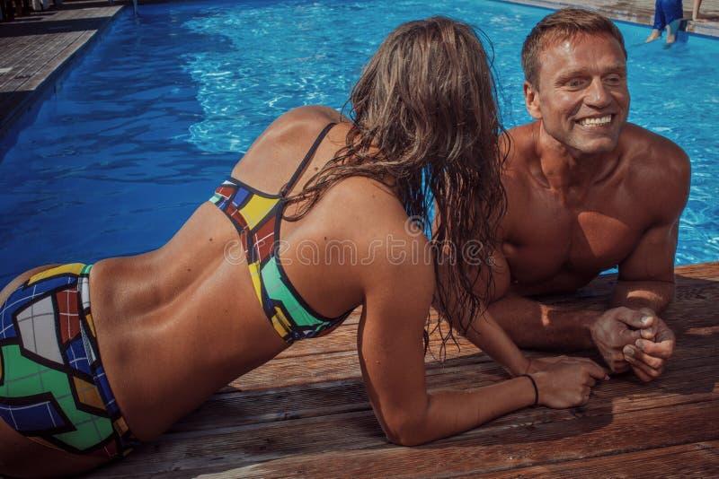Des couples attrayants, un mâle musculaire beau et une femme sexy détendant près de la piscine après la natation Apprécier des va photos libres de droits