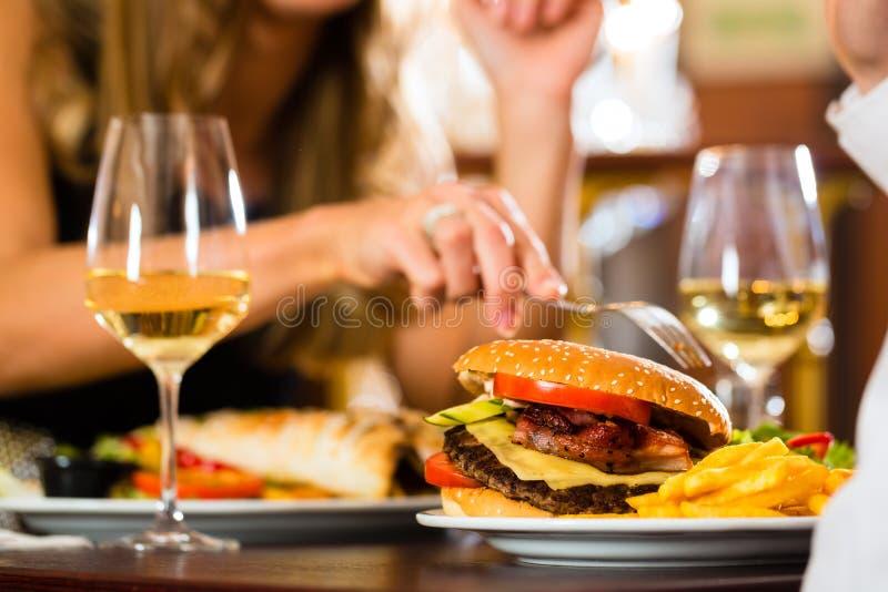 Les couples heureux dans le restaurant mangent des aliments de préparation rapide images libres de droits