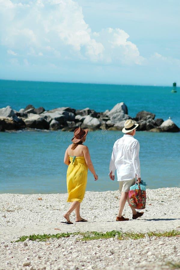 Des couples plus anciens marchant sur la plage photographie stock libre de droits