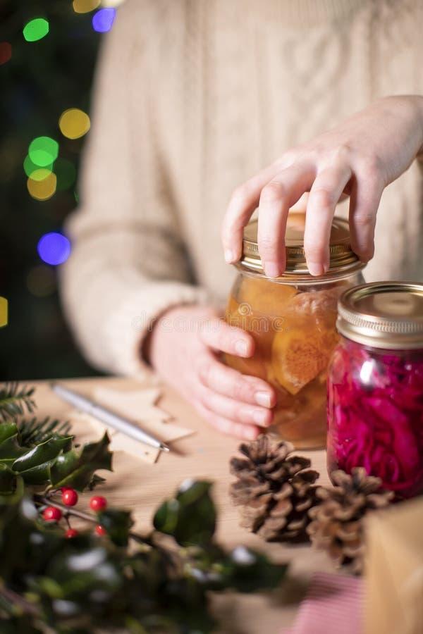 Des Couvercles De Foucault De Femme Sur Des Bocaux De Fruits Préservés À La Maison Pour Un Cadeau De Noël Éco-Convivial photographie stock