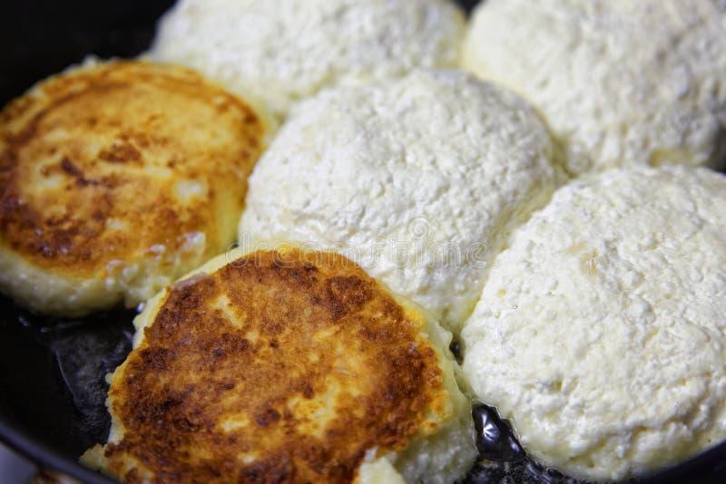 Des crêpes ou le syrniki faites maison de fromage sont faits frire dans une poêle Nourriture rustique traditionnelle en cuisines  image libre de droits