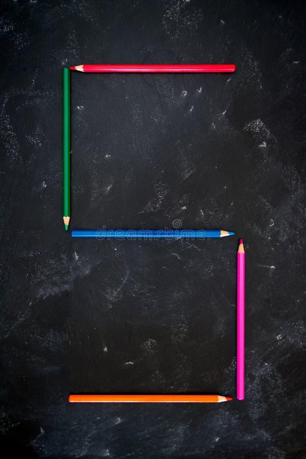 Des crayons de couleur sur le tableau noir de l'école faisant l'alphabet numérique 5 photographie stock libre de droits