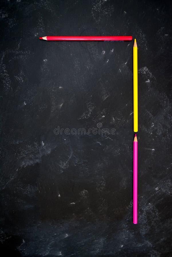 Des crayons de couleur sur le tableau noir de l'école faisant l'alphabet numérique 7 image libre de droits