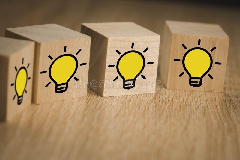 Des cubes en bois debout les uns au-dessus des autres avec l'image d'une lampe en feu, qui symbolise la nouvelle idée, le concept photographie stock