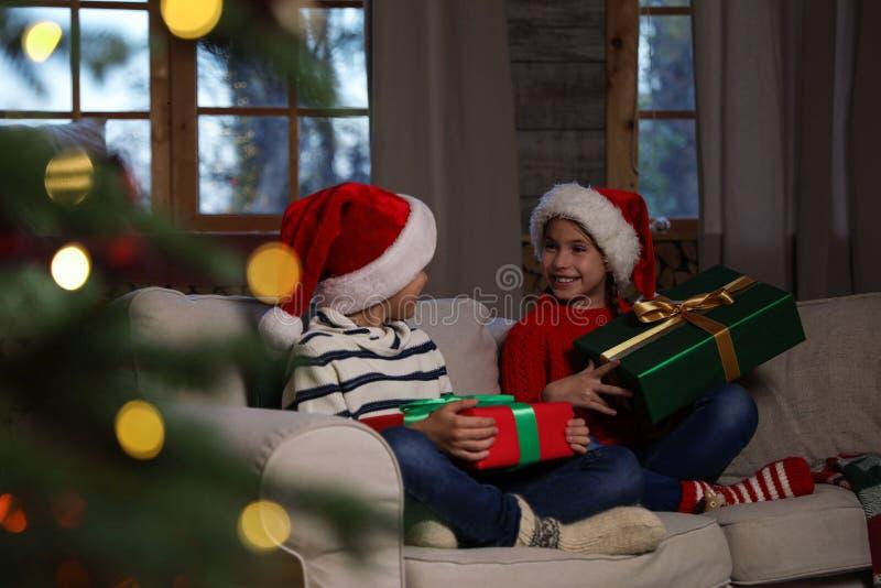 Des enfants heureux portant des chapeaux de Père Noël avec des cadeaux de Noël sur un canapé image libre de droits