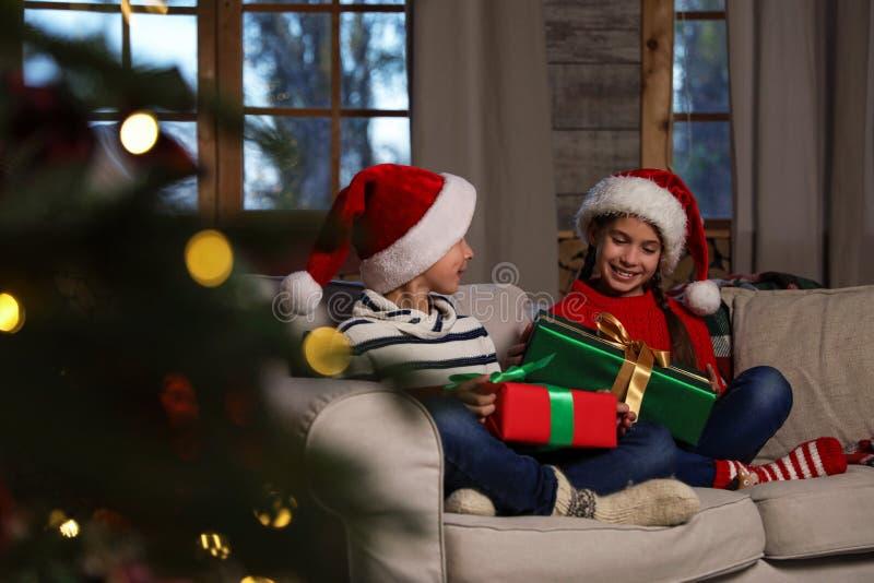 Des enfants heureux portant des chapeaux de Père Noël avec des cadeaux de Noël sur un canapé photographie stock libre de droits