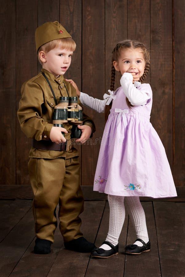 Des enfants sont habillés comme soldat dans de rétros uniformes militaires photos stock