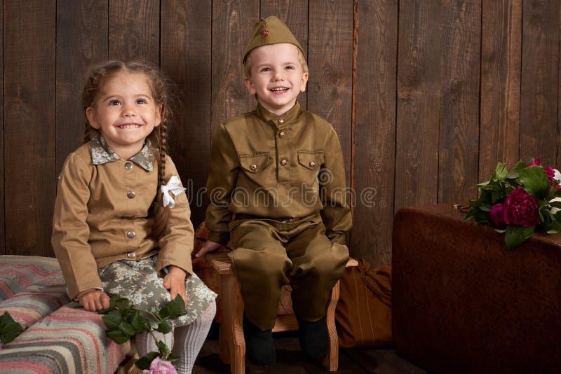 Des enfants sont habillés dans de rétros uniformes militaires envoyant un soldat à l'armée, fond en bois foncé, rétro style photos stock