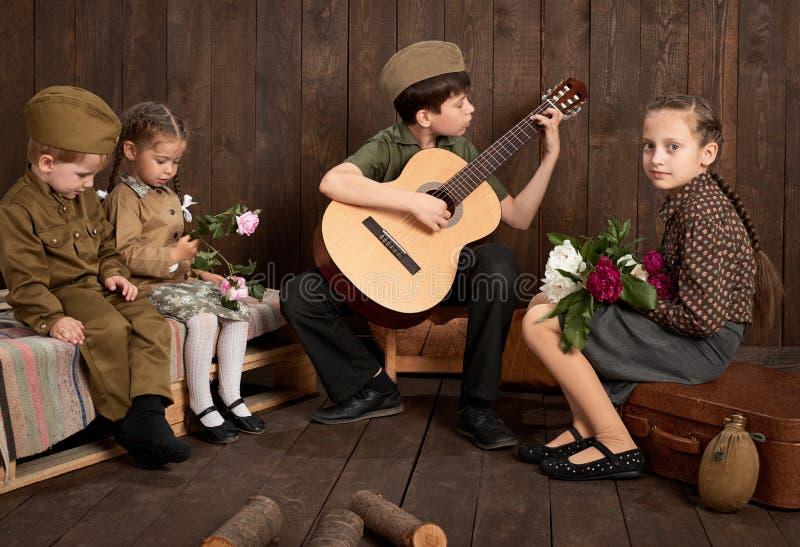 Des enfants sont habillés dans de rétros uniformes militaires reposant et jouant la guitare, envoyant un soldat à l'armée, le fon photo libre de droits