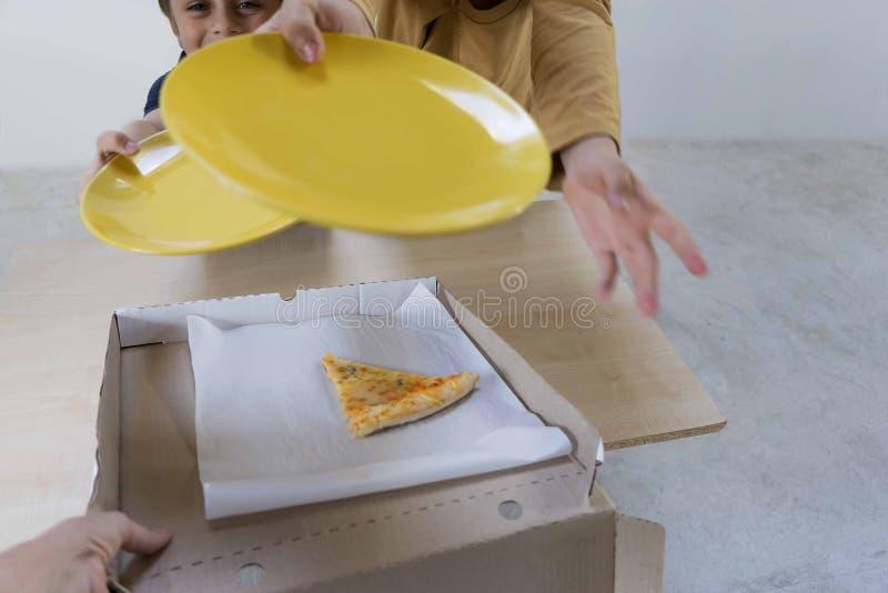 Des enfants sont invit?s ? leur donner le dernier morceau de fromages de la pizza 4 restant dans la bo?te apr?s un d?ner de famil photographie stock