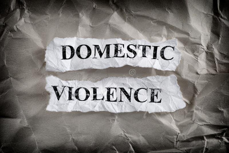 Des feuilles de papier déchirées avec les mots Violence domestique écrits sur elles sur un papier découpé photos stock