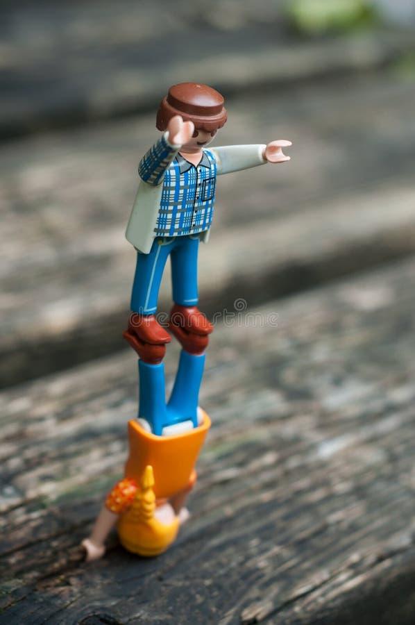Des figurines de playmobil debout en équilibre sur une table en bois à l'extérieur images libres de droits